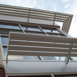 White aluminum sunshades on the side of a building.