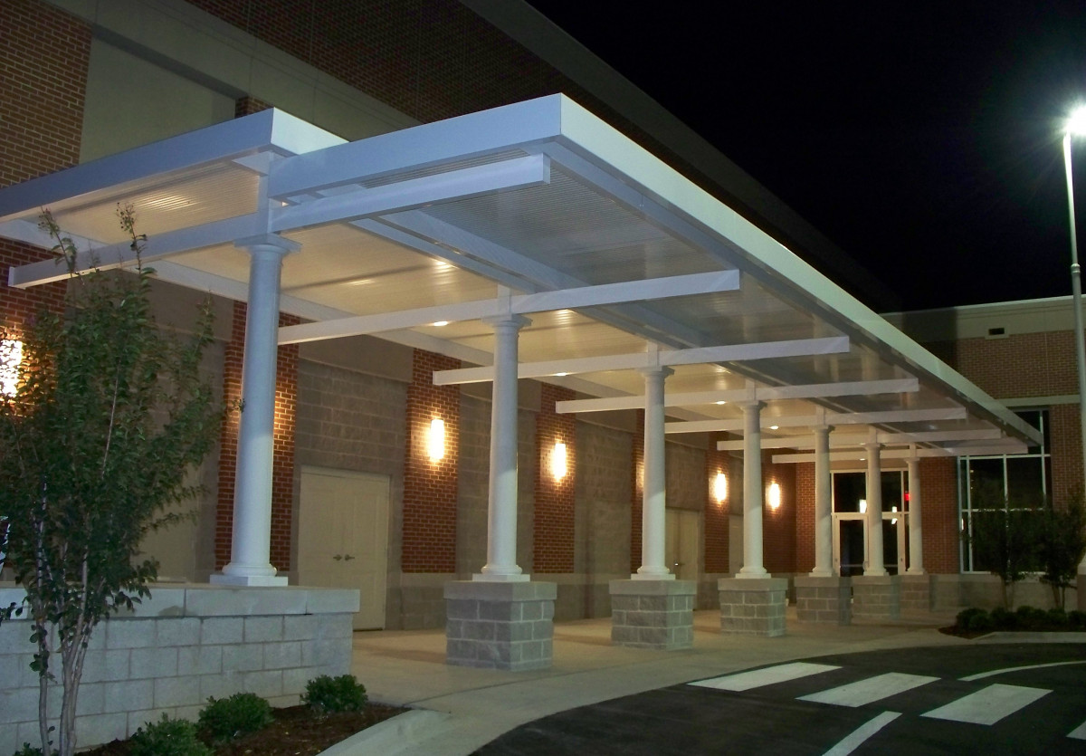 Custom, white aluminum walkway covers at night.