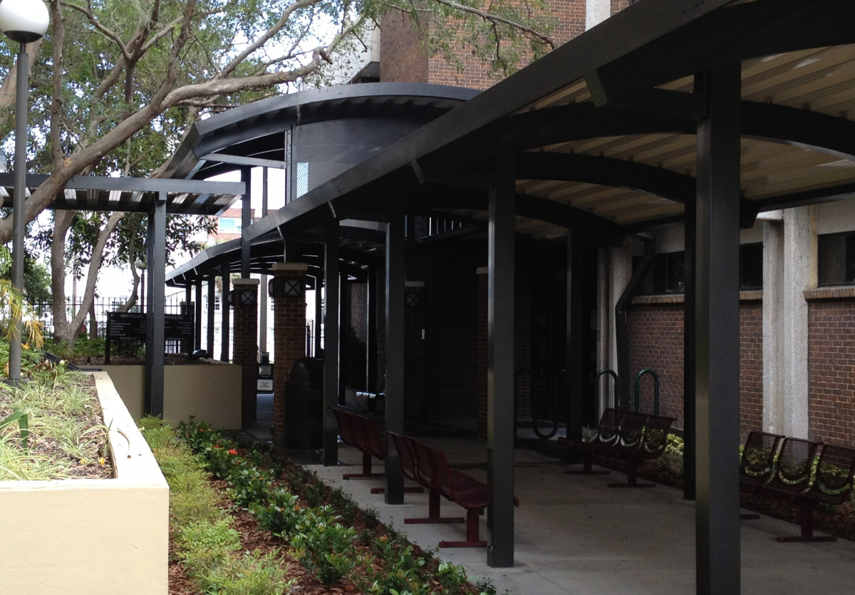 Custom made, black aluminum walkway covers beside a building.